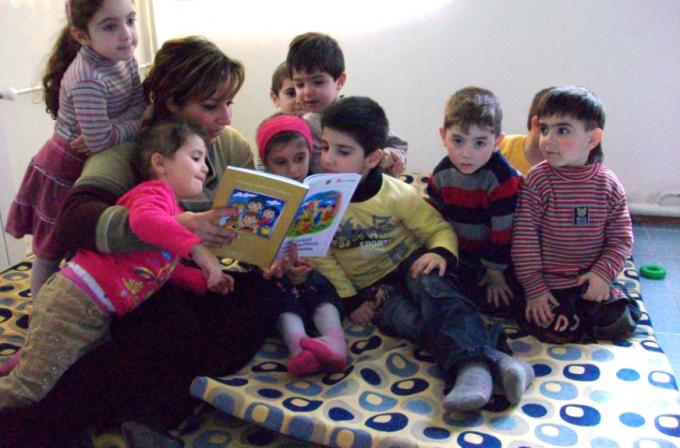Teacher reading a book for children at a preschool established for refugee and former refugee children