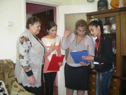 Izabella, 13, together with her classmate and teacher, advising community people on the correct placement of furniture to reduce the adverse effects of possible disasters